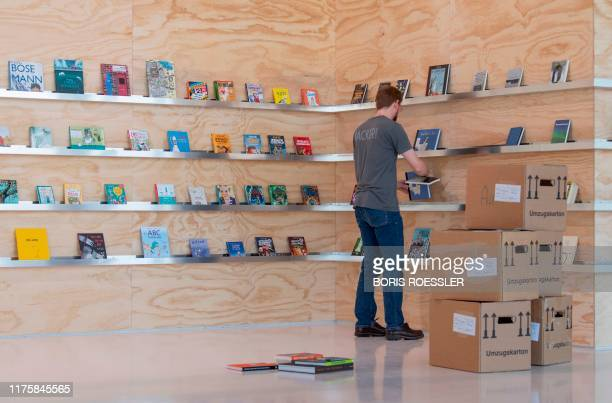 Man arranges books in a shelf at the booth of Norway as preparations are under way for the Frankfurt Book Fair in Frankfurt am Main, western Germany,...