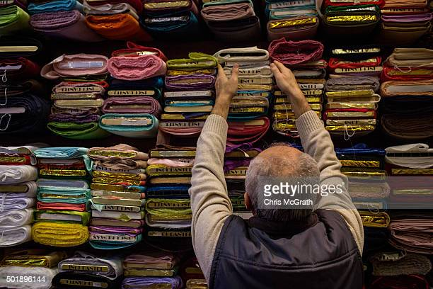 A man arranges fabric at a store outside the spice market on December 18 2015 in Istanbul Turkey Despite the expected growth in western and luxury...
