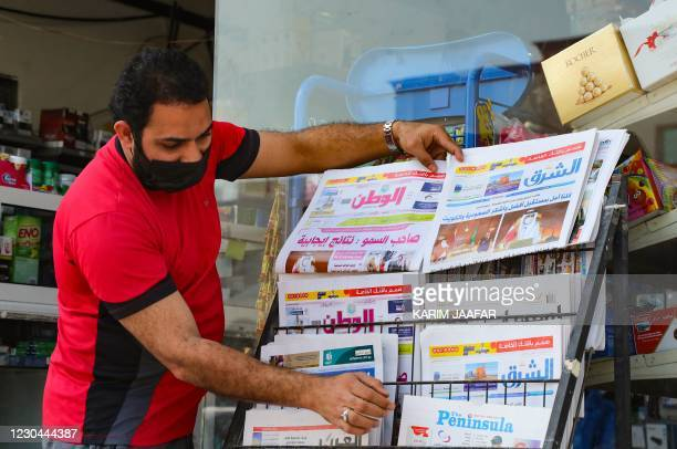 Man arranges newspapers on a stand outside a shop in the Qatari capital Doha showing headlines about the summit of the six-nation Gulf Cooperation...