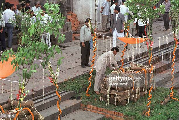 A man arranges sandlewood and marigold blossoms on a funeral pyre for a member of the Nepalese royal family June 2 2001 in Kathmandu Nepal before a...