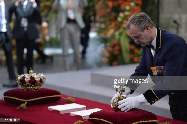 A man arranges the regalia at the credencetable prior to the inauguration of HM King Willem Alexander of the Netherlands and HRH Princess Beatrix of...