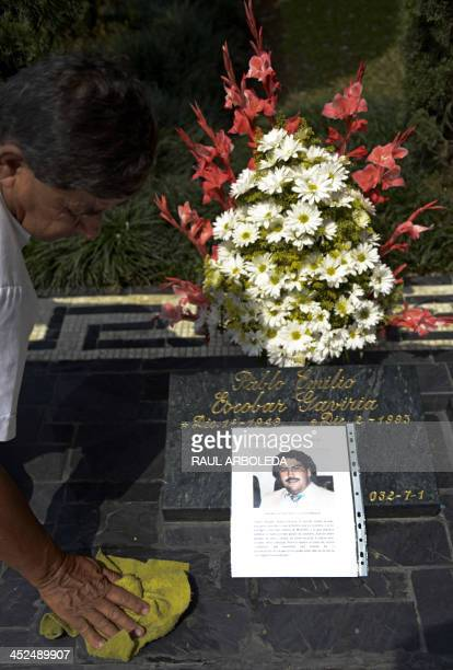 Man arranges the tomb of Colombian drug lord Pablo Escobar on November 29, 2013 at Montesacro cemetery in Medellin, Antioquia department, Colombia....