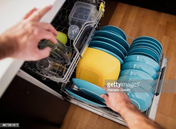 man arranging dishes in the dishwasher - utensílio de cozinha equipamento doméstico - fotografias e filmes do acervo