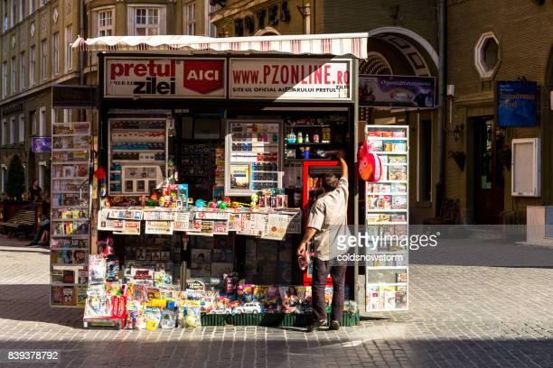 man arrangerar sina produkter på hans nyheter utmärker kiosk utomhus i brasov, transsylvanien, rumänien - rumänien bildbanksfoton och bilder