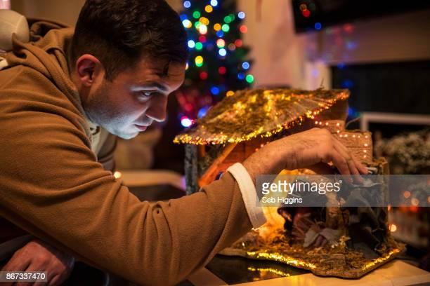 Man arranging nativity scene