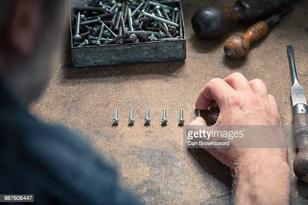 Man arranging screws of similar size in a row