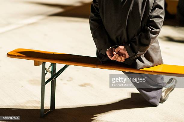 A man arrested on the suspicion of smuggling migrants from Austria into Germany sits handcuffed on a bench in the early hours on the A3 highway on...