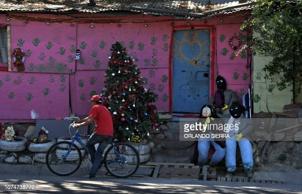 TOPSHOT A man arrives at his house decorated with a Christmas tree and dummies in the hamlet of Germania on the outskirts of Tegucigalpa on December...