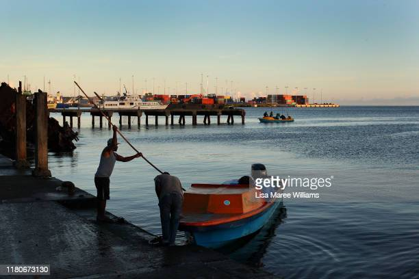A man arrives at the Honiara Central Markets by boat as performers from the 'Solomon Islands Cultural Group' prepare to leave the island nation to...