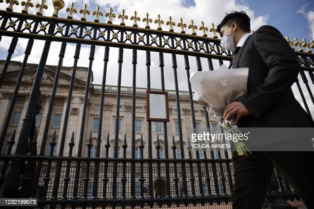 Man arrives to lay a bunch of flowers outside Buckingham Palace in central London on April 9, 2021 after the announcement of the death of Britain's...