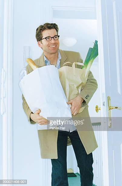 Man arriving home carrying shopping, smiling