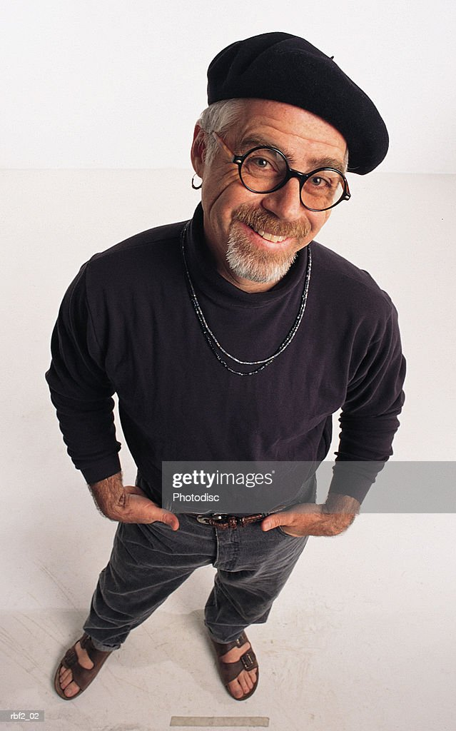 A man artist dressed all in black has his hands in his pocket as he looks upward toward the camera : Stockfoto