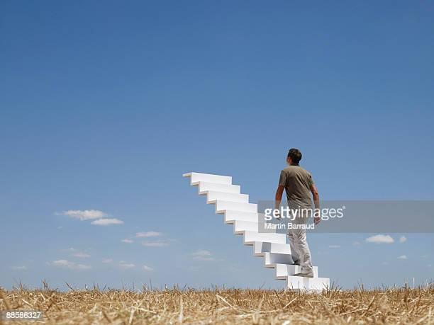 Man ascending stairway to sky