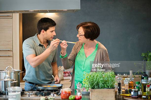 Man asking his mother to taste his cooking