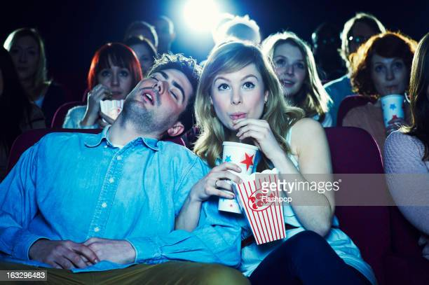 Man asleep at the movies with his girlfriend