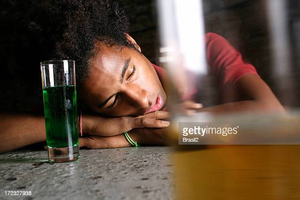 Man asleep in front of two alcoholic beverages