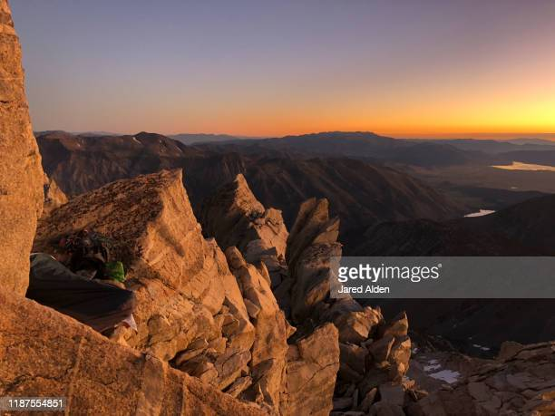man asleep in sleeping bag on high rocky mountain top ridge during sunrise on the cliffs of the matterhorn peak overlooking the sawtooth ridge on the border of inyo national forest and yosemite national park - pinnacle peak stock pictures, royalty-free photos & images