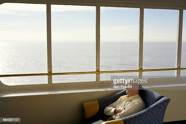 man asleep inside ferry boat lounge - ferry stock pictures, royalty-free photos & images