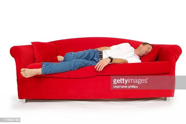 homme endormi sur un canapé rouge avec fond blanc - dormir humour photos et images de collection