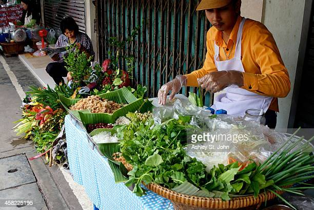 Man assembles rice paper wraps with fresh ingredients in the Mae Klong Market in Samut Songkhram, Thailand in October 2013.