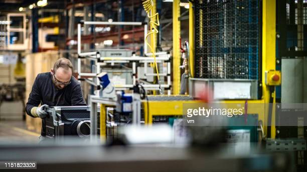 man assembling a washing machine in a factory - industry stock pictures, royalty-free photos & images
