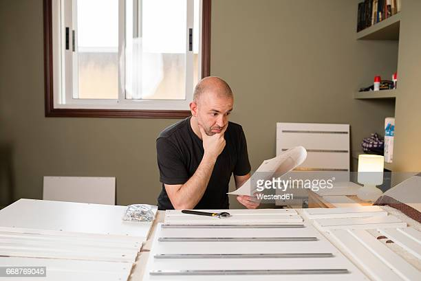 man assembling furniture at home, reading instructions - instructions stock pictures, royalty-free photos & images