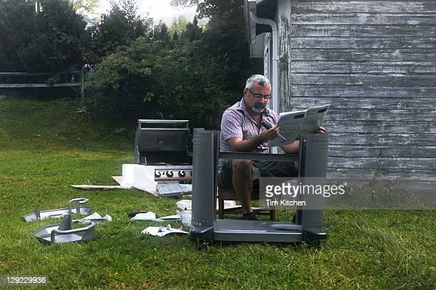 Man assembling grill, looking at instructions