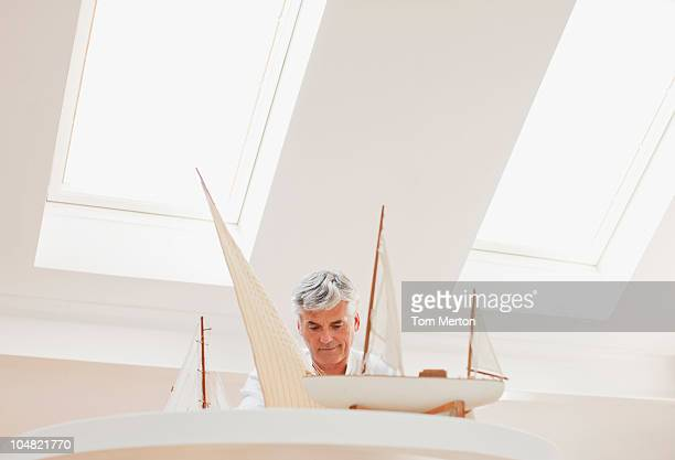 Man assembling model sailboat