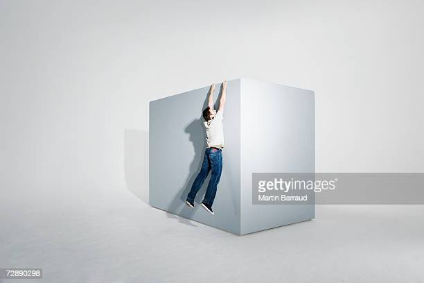 Man assisting colleague climbing on giant box