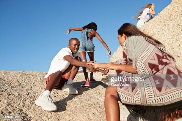 man assisting friend in climbing rock - doing a favor stock pictures, royalty-free photos & images