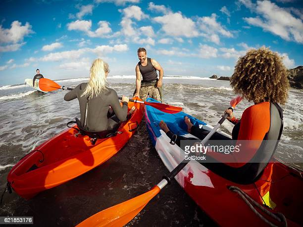 Man Assisting Girls in Kayak out to sea