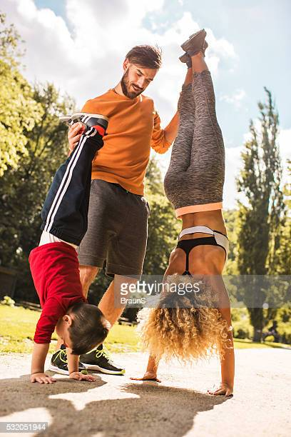 Man assisting his wife and son in doing a handstand.