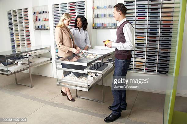 Man assisting two women selecting colour samples in shop