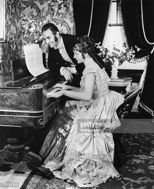 Man assisting woman playing on spinet (B&W)