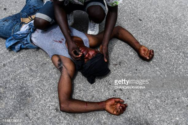 TOPSHOT A man assists a demonstrator bleeding from a wound on his head and lying on the pavement during a protest march against the ruling government...