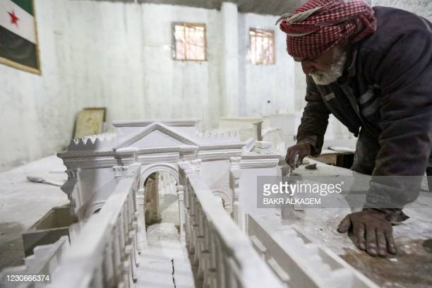 Man assists Ali Saleh , a 58-year-old displaced Syrian originally from Palmyra, as they build from memory a wood and gypsum model of a prominent...