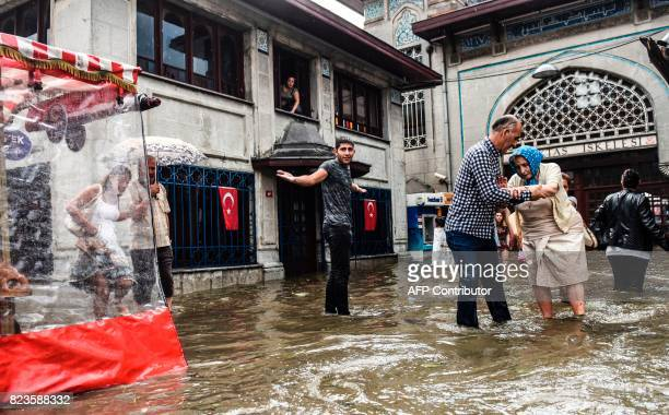 A man assists an elderly woman in a flooded street after a heavy downpour of rain and hail at Besiktas near Istanbul on July 27 2017 / AFP PHOTO /...