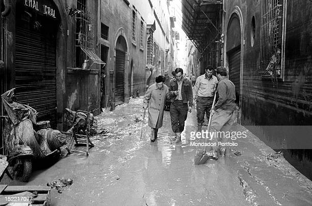 A man assists an old lady across the muddy expanse while other two citizens work to clean streets and houses ather the flood Florence 1966
