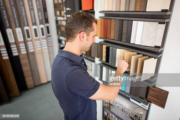 man at a floor store looking at wood samples - fliesenboden stock-fotos und bilder
