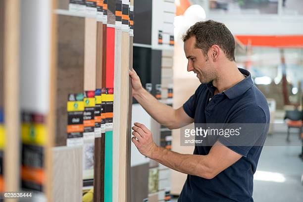 Man at a floor store looking at wood samples