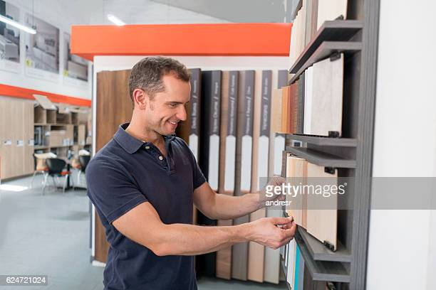 man at a floor store looking at wood samples - showroom stock pictures, royalty-free photos & images