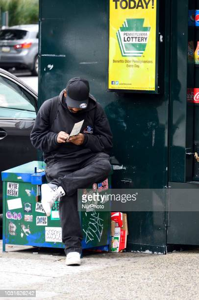 Man at a news stand checks a lotto ticket in Philadelphia PA on September 11 2018