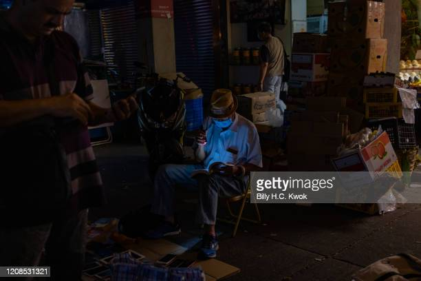 A man at a night market wearing face masks as a precaution against the spread of Coronavirus during a coronavirus on March 28 2020 in Hong Kong China...