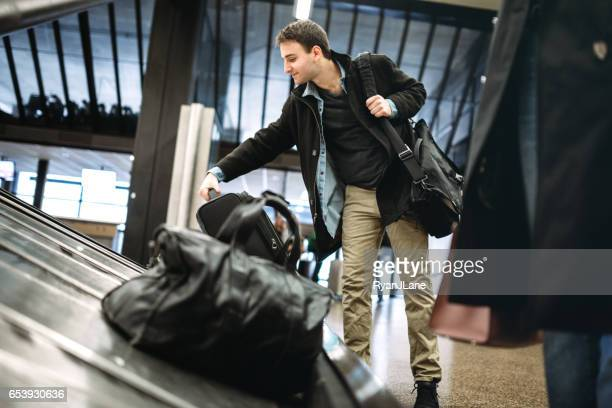 man at airport baggage pick-up - baggage claim stock pictures, royalty-free photos & images