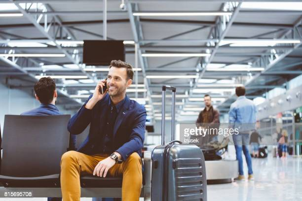 man at airport lounge and using mobile phone - business travel stock pictures, royalty-free photos & images