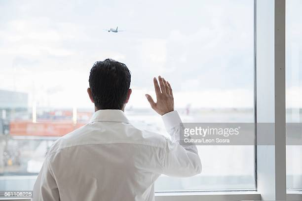 Man at airport window, waving