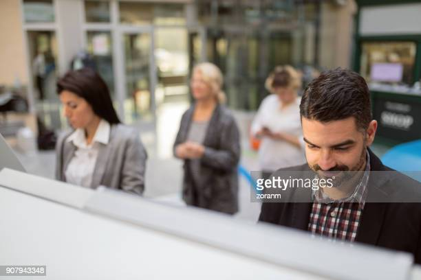 man at atm - bank financial building stock pictures, royalty-free photos & images