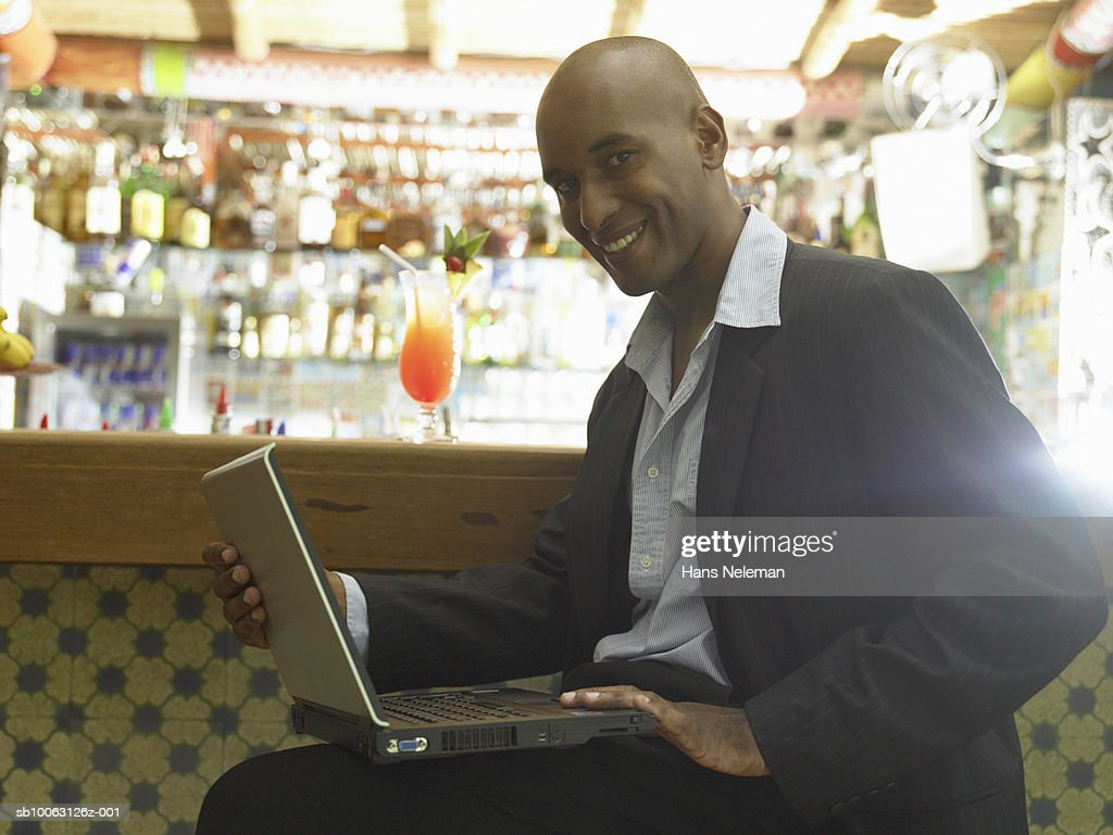 Man at bar with laptop, smiling, portrait : Stock Photo