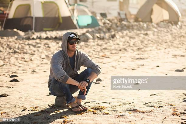 Man at beach camp, Malibu, California, USA