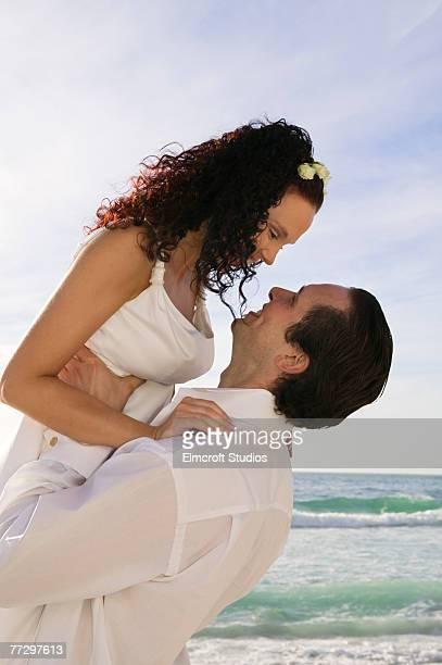 Man at beach lifting woman up